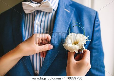 Hands adjusting yellow boutonniere pinned to a grooms blue jacket