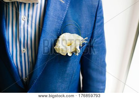 Yellow boutonniere pinned to a grooms blue jacket