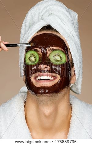 Smiling man receiving spa treatments. Photo of young man with pieces of kiwi in his eyes and chocolate face mask. Beauty & Skin care concept