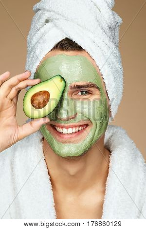 Handsome man holding half an avocado in hand. Photo of man with moisturizing facial mask. Beauty & Skin care concept