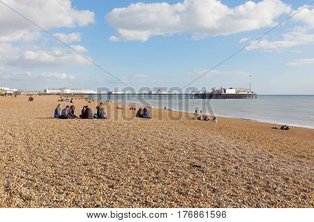 BRIGHTON GREAT BRITAIN - FEB 24 2017: People sitting in groups on the Brighton beach. The Brighton pier in the background. February 24 2017 in Brighton Great Britain