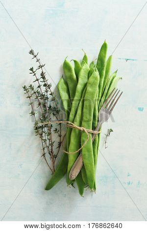 Bunch of green beans with thyme and fork, on table.