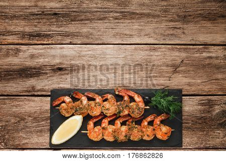 Appetizing shrimps served on black slate, flat lay. Wooden rustic table background with copy space for text. Japanese seafood, mediterranean cuisine concept