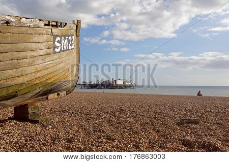 BRIGHTON GREAT BRITAIN - FEB 24 2017: Brighton beach a boat in the foreground and the Brighton pier in the background. February 24 2017 in Brighton Great Britain