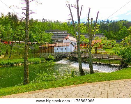 View on waterfall, mill in white building, pedestrian bridge in Park Postojna jama near Postojna Cave, famous attraction in Slovenia.