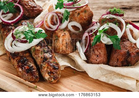 Appetizing assortment of grilled meat on pita bread decorated with onion and herbs, close up view. Restaurant menu photo.