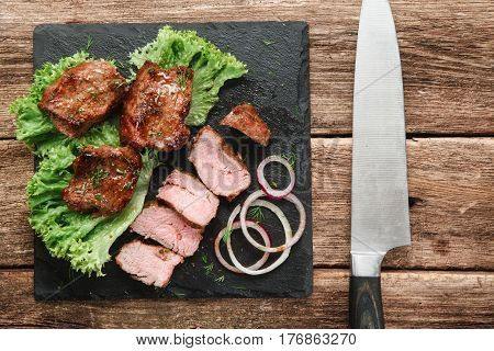 Tasty shashlik served with green salad and onion rings on black slate with big knife, on rustic wooden table, flat lay. Restaurant menu photo.