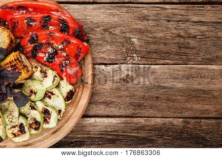 Wooden platter with grilled vegetables on rustic wooden table, top view. Free space for text. Menu photo. Healthy lifestyle, vegetarian cuisine concept