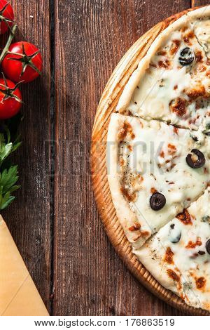 Traditional italian food. Delicious fresh pizza on rustic wooden table with ingredients, top view. Vertical photo.