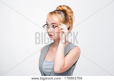 Young woman in glasses looks distrustful, doubtful, timid and apprehensive. Grey background with copy space.