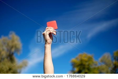 sport, caution, game and people - close up of referee hands with whistle showing red card on football field