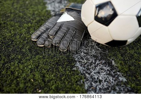 sport, soccer and game - ball and goalkeeper gloves on football field
