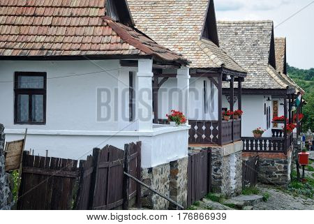 Row of farmhouses with porches decorated with flowers in Holloko, Hungary