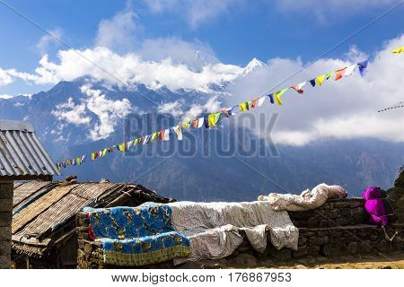 View of Mountains with high snowy peaks and blue sky with traditional Nepalese flags garland and roofs of primitive masonry buildings of trekking lodge on foreground.