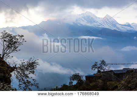 Sunset Mountain View with Clouds around high Peaks and small Trees Silhouette on foreground in natural color tone