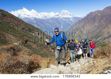 Group of People of different age and ethnicity walking up on Mountain Trail during Hike in Nepalese Himalaya carrying heavy backpacks and climbing gear led by mature Guide.