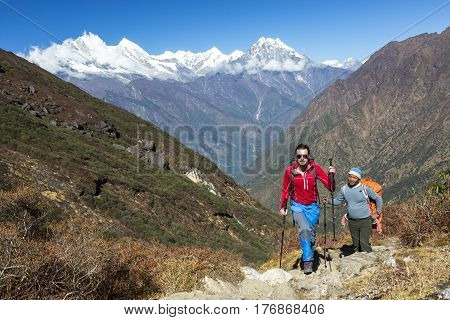 Young Hiker in red Jacket and blue Pants walking on Mountain Trail along with local Sherpa Guide. High snowy Peaks View and blue Sky on Background