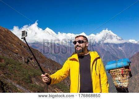 Bearded Man in bright sporty Jacket taking Photo Self Portrait or Video with compact Camera holding it with Stick Mountain Panorama and local Porter carrying heavy Luggage on Background.