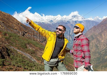 Two smiling Men in sporty clothing staying on Mountain Trail and pointing with Hand on Summit or further Way high snowy Peaks and Valley on Background.