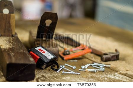 carpenter tools in pine wood table Hammer, pliers and metallic nails. Nail head in focus. Carpentry works.