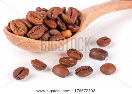 Coffee beans in a wooden spoon isolated on a white background.