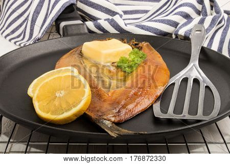 scottish smoked kipper with lemon butter and parsley on a pan