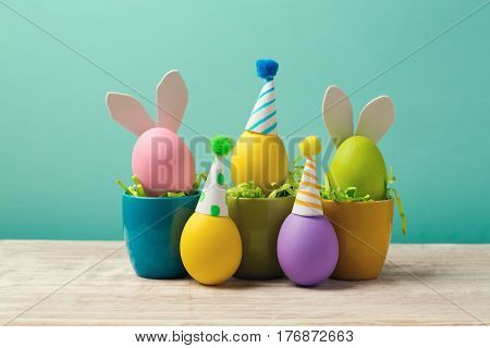 Easter holiday concept with cute handmade eggs in coffee cups bunny ears and party hats on wooden table