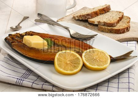 scottish smoked kipper with lemon butter and parsley on a plate