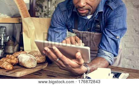 Adult Man Using Tablet in Bakery Shop