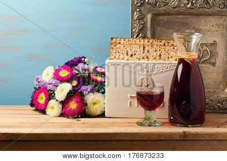 Jewish holiday passover concept with wine matzoh vintage plate and spring flowers over wooden background