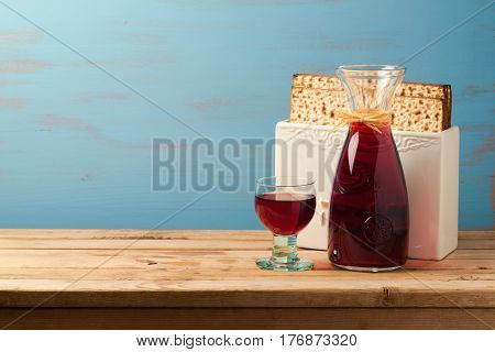 Jewish holiday passover concept with wine and matzoh over wooden blue background with copy space