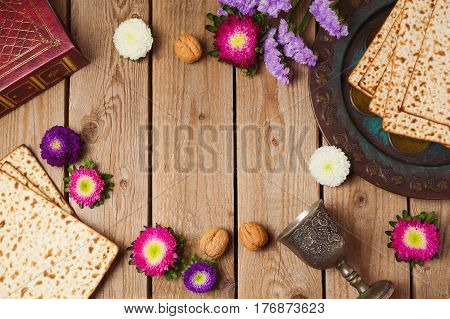 Jewish holiday Passover concept with matza and seder plate over wooden background. View from above