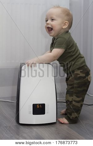 An infant kid staying leaning against the humidifier. Laughing and smiling lovely toddler.