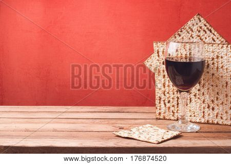 Passover holiday background with wine glass and matzoh on wooden table with copy space