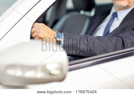 transport, business, time and people concept - senior businessman hands with wristwatch driving car