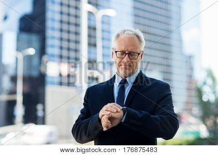 business, punctuality and people concept - senior businessman checking time on wristwatch or smart watch on his hand in city