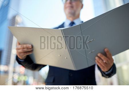 business, office work and people and concept - senior businessman with documents in ring binder folder on city street