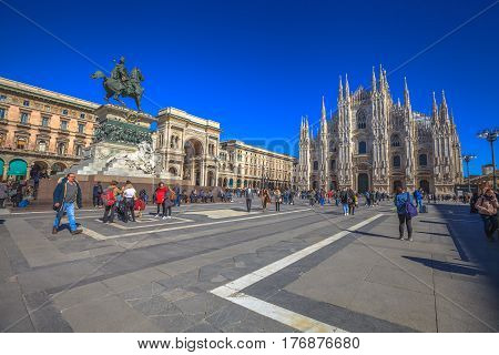 MILAN, ITALY- MARCH 7, 2017: Dome square with Duomo di Milano Cathedral in a blue sky day. Tourists and the equestrian statue of Vittorio Emanuele II and gallery Vittorio Emanuele II.