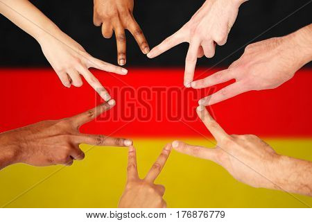 diversity, immigration, ethnicity, international and people concept - group of hands showing peace hand sign over german flag background