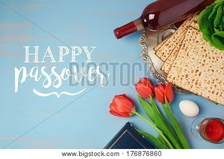Jewish holiday Passover Pesah greeting card with seder plate matzoh and tulip flowers on wooden background