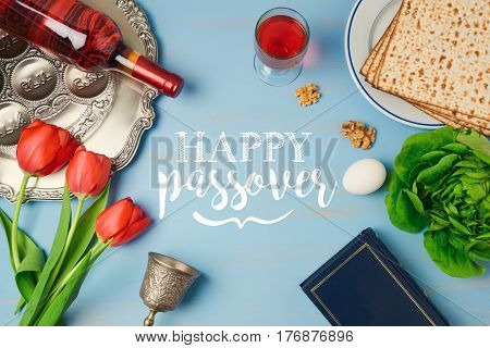 Jewish holiday Passover Pesah greeting card with seder plate matzoh tulip flowers and wine bottle on wooden background. View from above