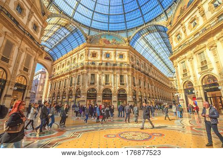 MILAN, ITALY- MARCH 7, 2017: crossroad of the Galleria Vittorio Emanuele II arcaded mall with people and famous fashion stores like Prada, in Dome square. Luxury, leisure and shopping concept.