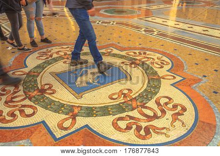 MILAN, ITALY- MARCH 7, 2017: Tourists stepping on the Bull's Balls of mosaic in Milano inside Galleria Vittorio Emanuele II gallery in Duomo square. This tradition practice may bring good luck.