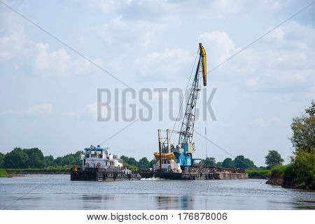 The cargo barge floats on the river.