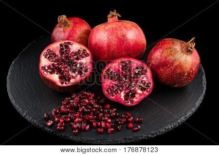 Three pomegranates and seeds on black plate with black background
