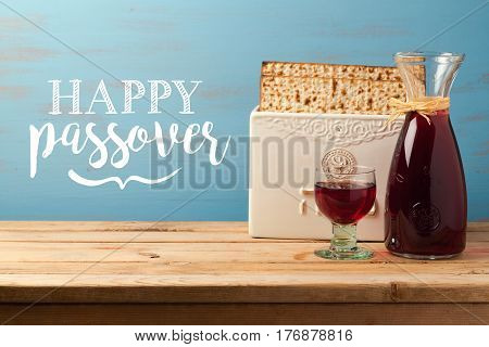 Jewish holiday Passover Pesah greeting card with wine and matzoh over wooden background