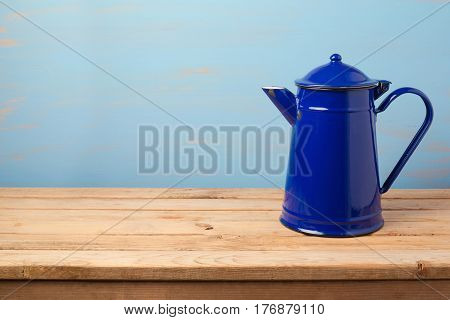 Vintage enamel coffee pot on wooden table over painted wall background