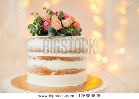 Decorated by flowers white naked cake, rustic style for weddings, birthdays or events.