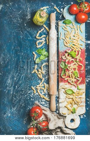 Ingredients for cooking Italian dinner. Fresh pasta casarecce, tomatoes, basil leaves, bottle of olive oil on colorful wooden board over dark blue background. Top view, copy space. Food frame concept