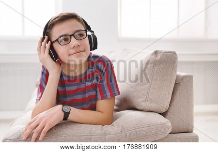 Leisure activity, teenager enjoy music - portrait of dreamy kid in headphones while lying on sofa indoors. Relax time - teenage boy listen to music on couch at home